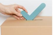 Hand mit Haken und Wahlbox